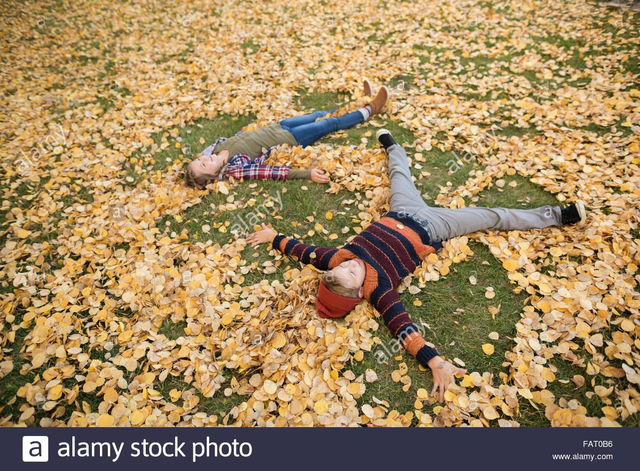 Frère et soeur de faire des anges dans les feuilles d'automne Photo Stock