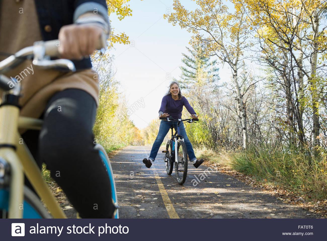 Carefree woman riding bike avec jambes écartées Banque D'Images