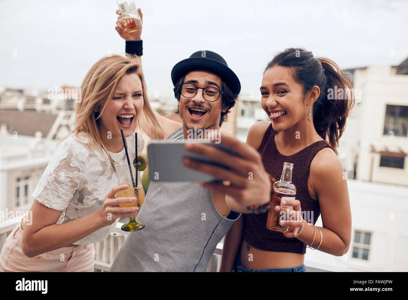 Petit groupe d'amis en tenant sur un selfies téléphone mobile. Jeune homme et femmes avec boissons faire drôle de Banque D'Images