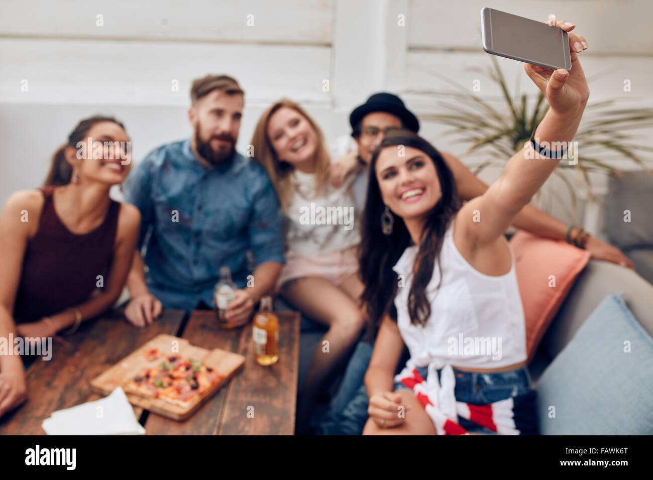 Groupe d'amis ayant une partie sur le toit en faisant un à se souvenir de ce parfait selfies moment. Heureux Photo Stock