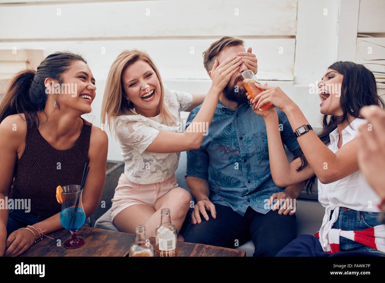 Jeunes amis assis jouissant ensemble partie. Femme fermeture yeux d'un homme avec un autre donner à boire. Photo Stock