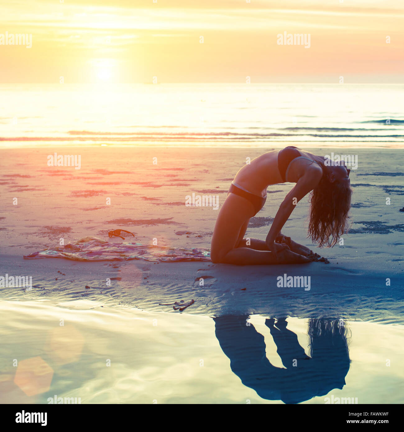 Jeune fille effectue des exercices de yoga sur la plage au coucher du soleil. Le yoga, la forme physique et un mode Photo Stock