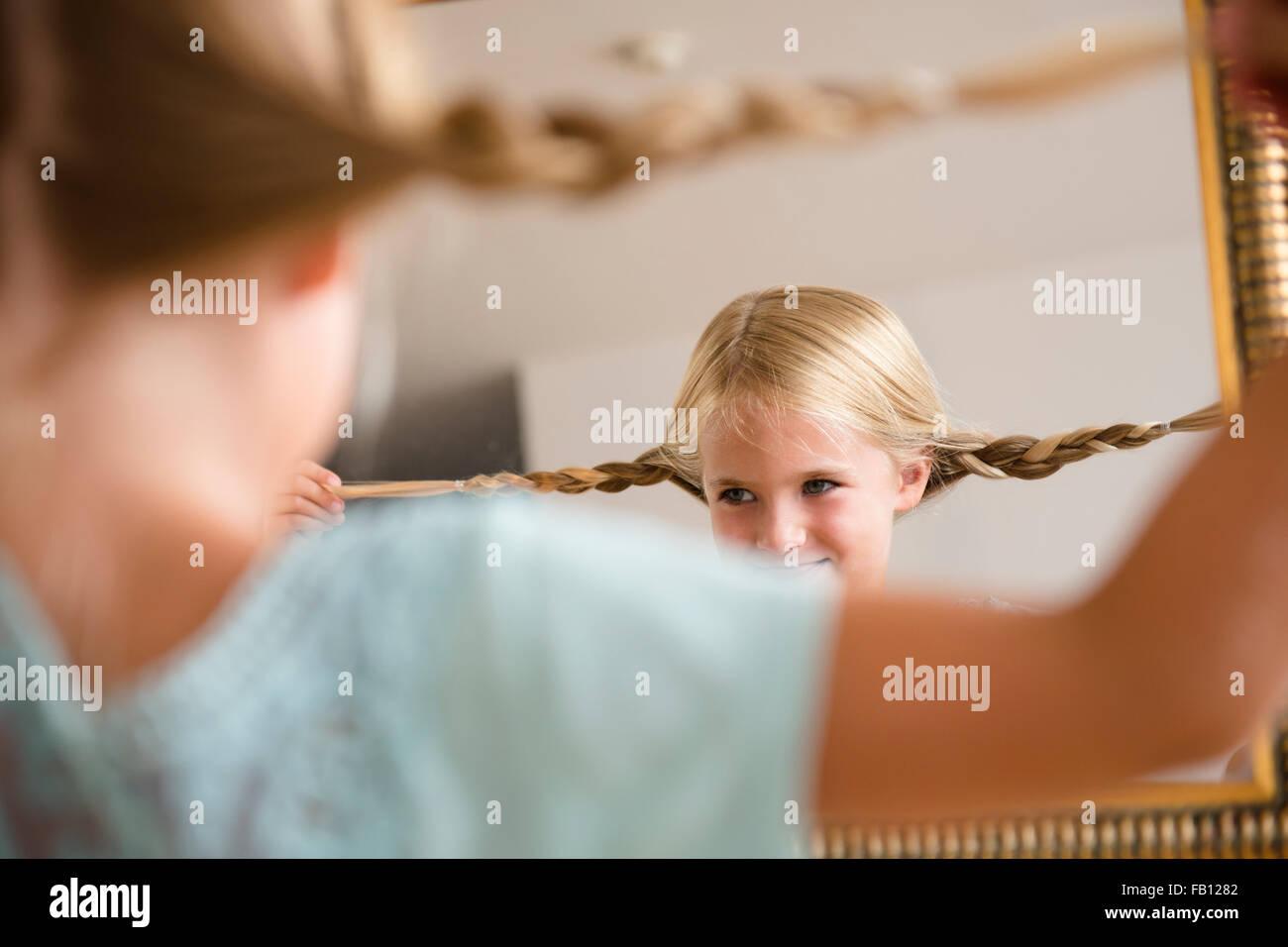 Girl (6-7) ce qui reflète en miroir Photo Stock