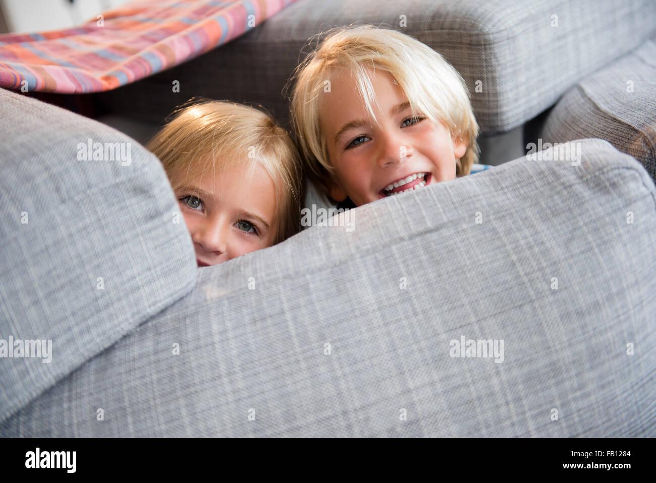 Boy (4-5) et (6-7) se cacher derrière les oreillers Photo Stock