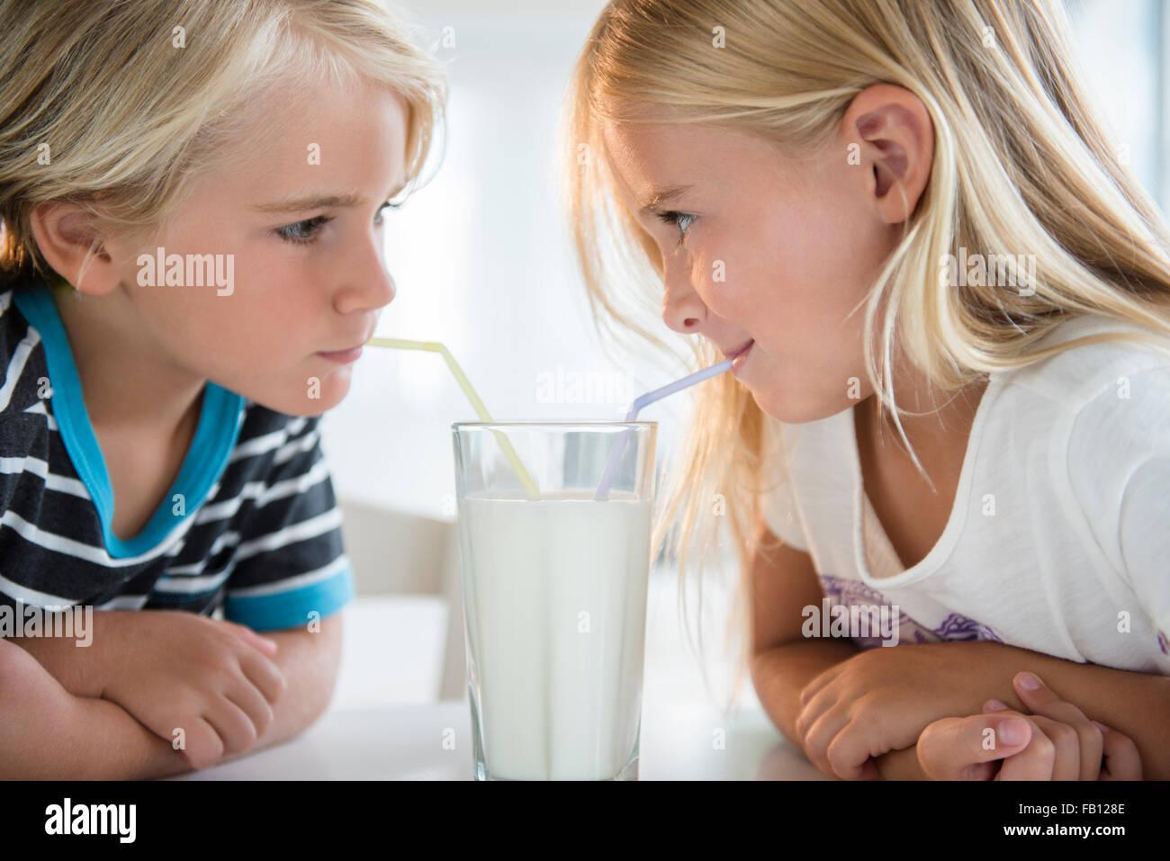 Frère (4-5) avec sa sœur (6-7) boire du lait à partir du verre Photo Stock