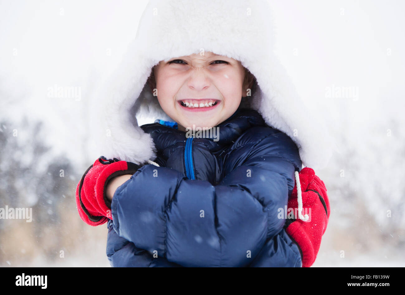 Portrait of boy (6-7) in fur hat et gants Photo Stock