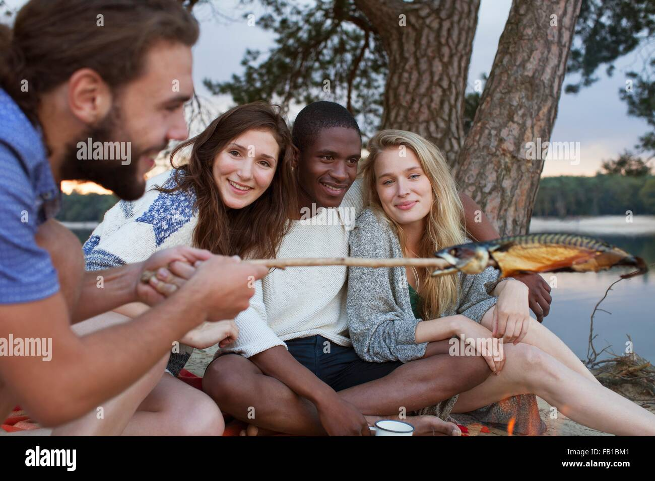 Des couples camping by lake Photo Stock