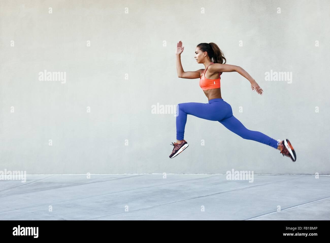 Vue latérale du jeune femme portant des vêtements de sport au milieu de l'air position marche Photo Stock