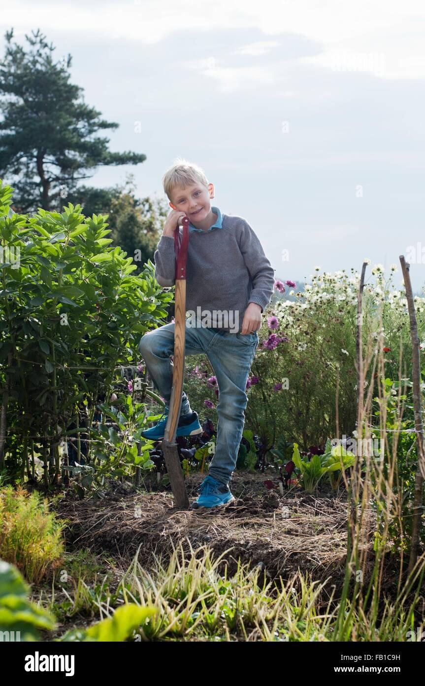 Portrait of boy creuser dans le jardin biologique Photo Stock