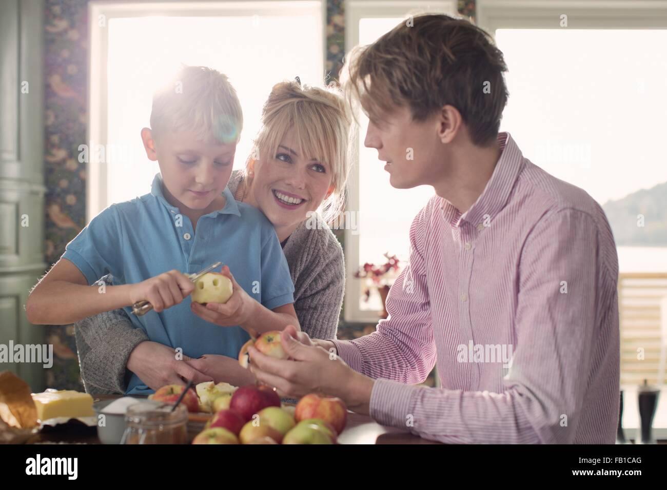 Les parents et les fils l'épluchage des pommes biologiques dans la cuisine Photo Stock