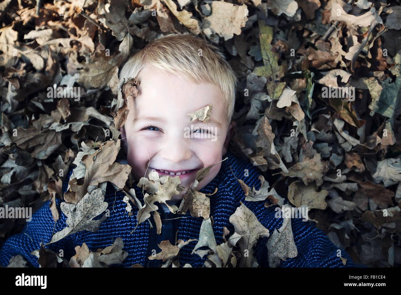 Vue de dessus de garçon couché recouvert de feuilles d'automne smiling at camera Photo Stock