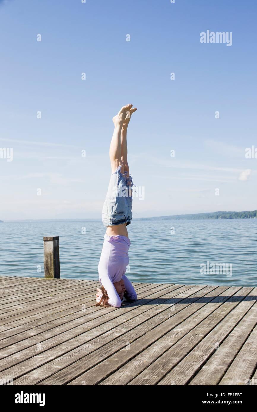 Femme mature sur pier par tête en équilibre sur l'océan Photo Stock