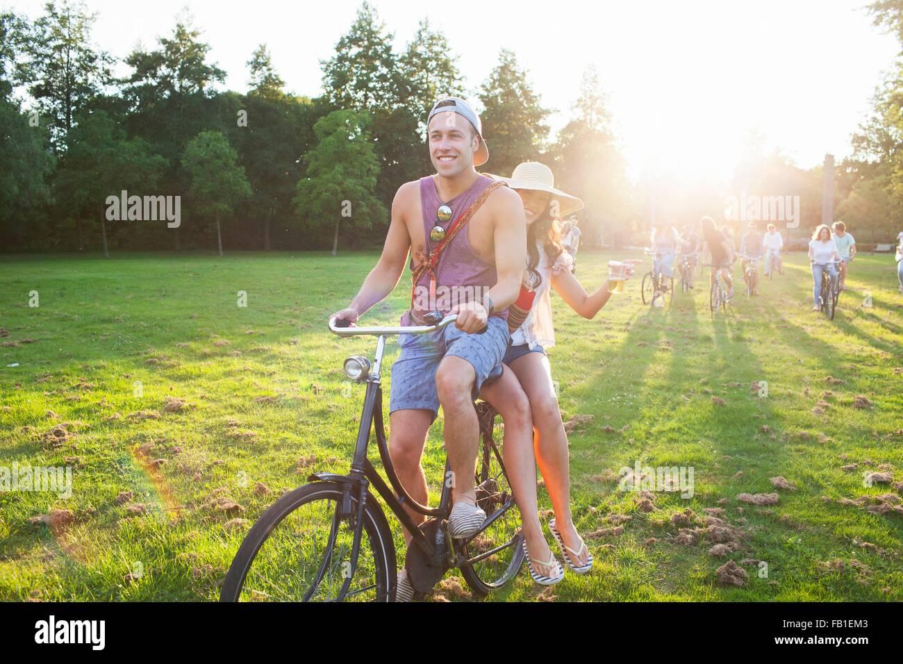 Foule de partygoing adultes arrivant sur des cycles à Sunset Park partie Photo Stock