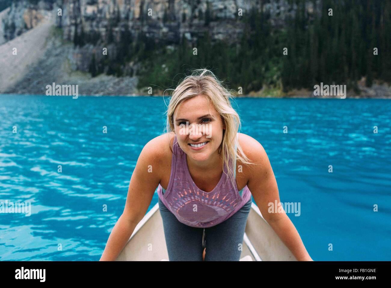 Portrait of mid adult woman en canoë sur le lac Moraine, smiling at camera, Banff National Park, Alberta Canada Banque D'Images