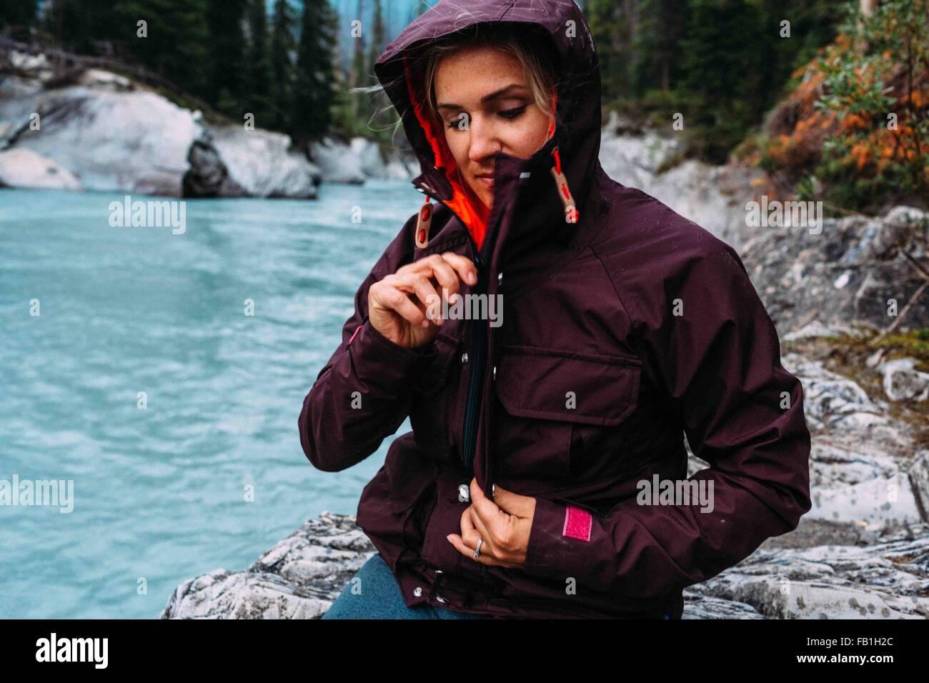 Mid adult woman par waters edge zipping up manteau imperméable, lac Moraine, Banff National Park, Alberta Canada Photo Stock