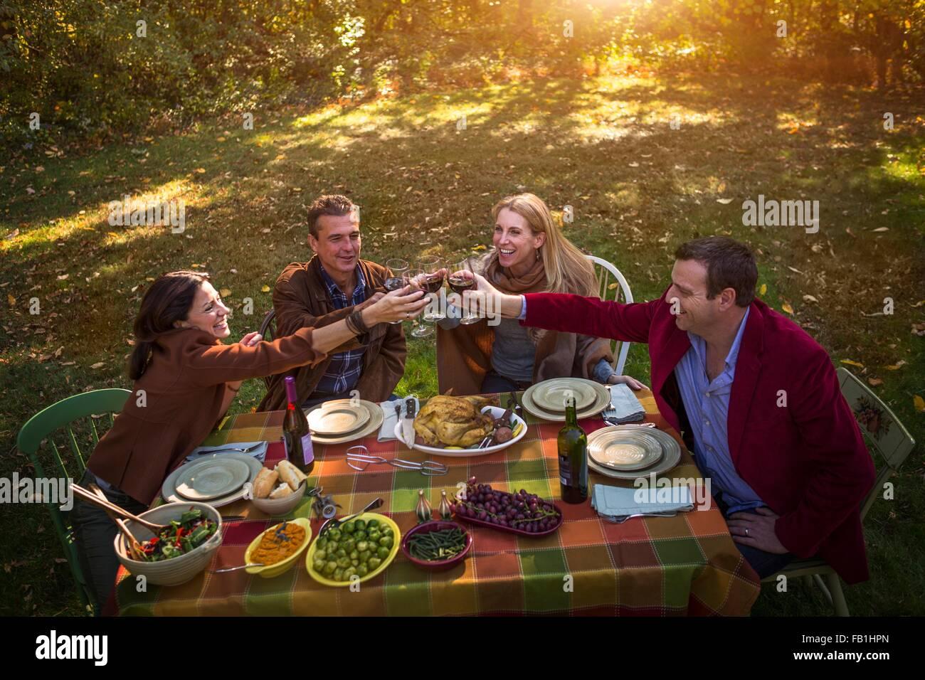 Deux couples d'âge mûr faire un toast at garden dinner party Photo Stock