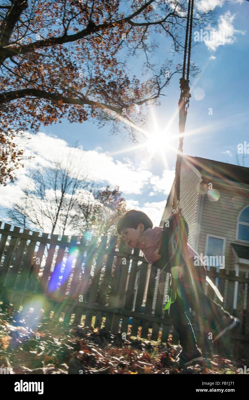 Vue de côté de l'angle faible Garçon jouant sur la balançoire dans le jardin Photo Stock