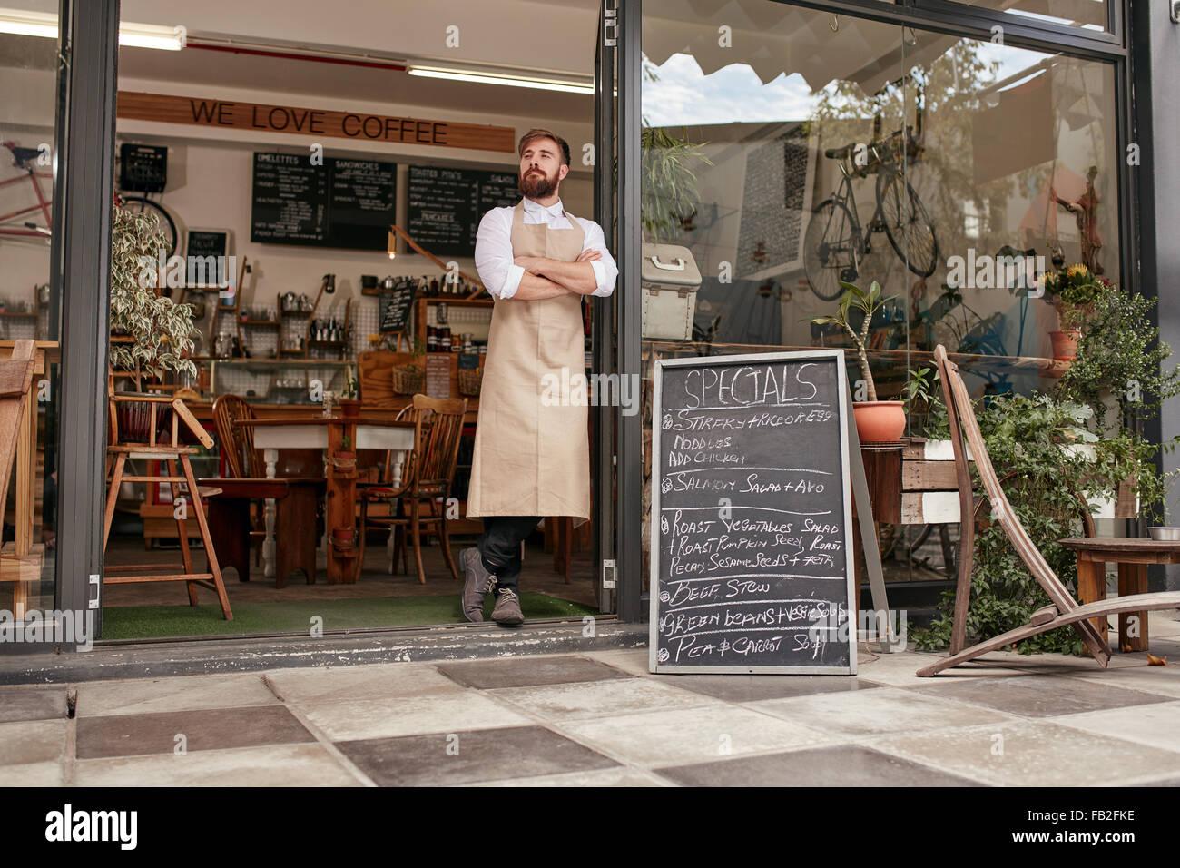 Tirer sur toute la longueur d'un barista jeunes debout dans porte d'un café. Jeune homme avec barbe Photo Stock