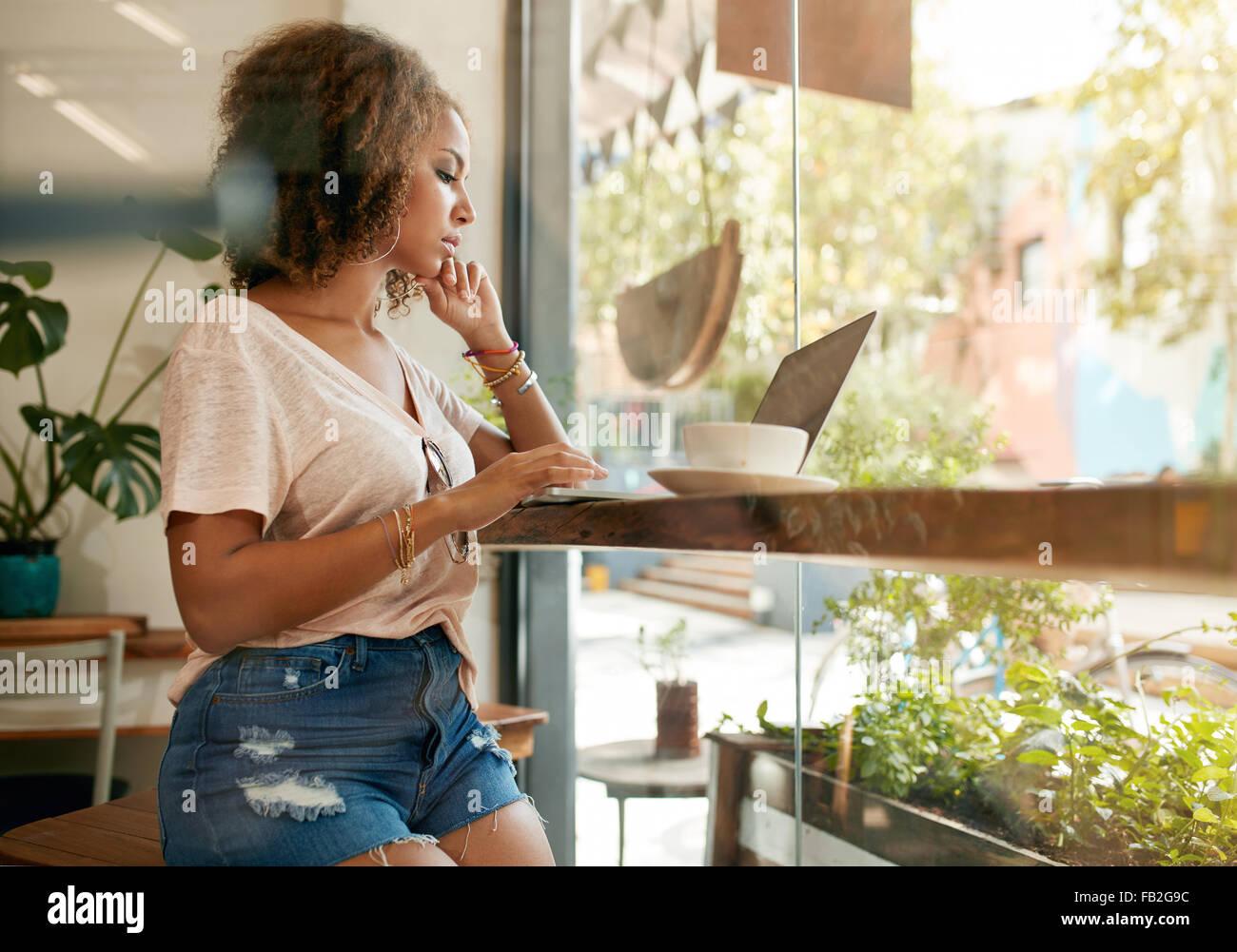 Tourné d'une jeune femme à l'aide de son ordinateur portable dans un café. Femme africaine Photo Stock