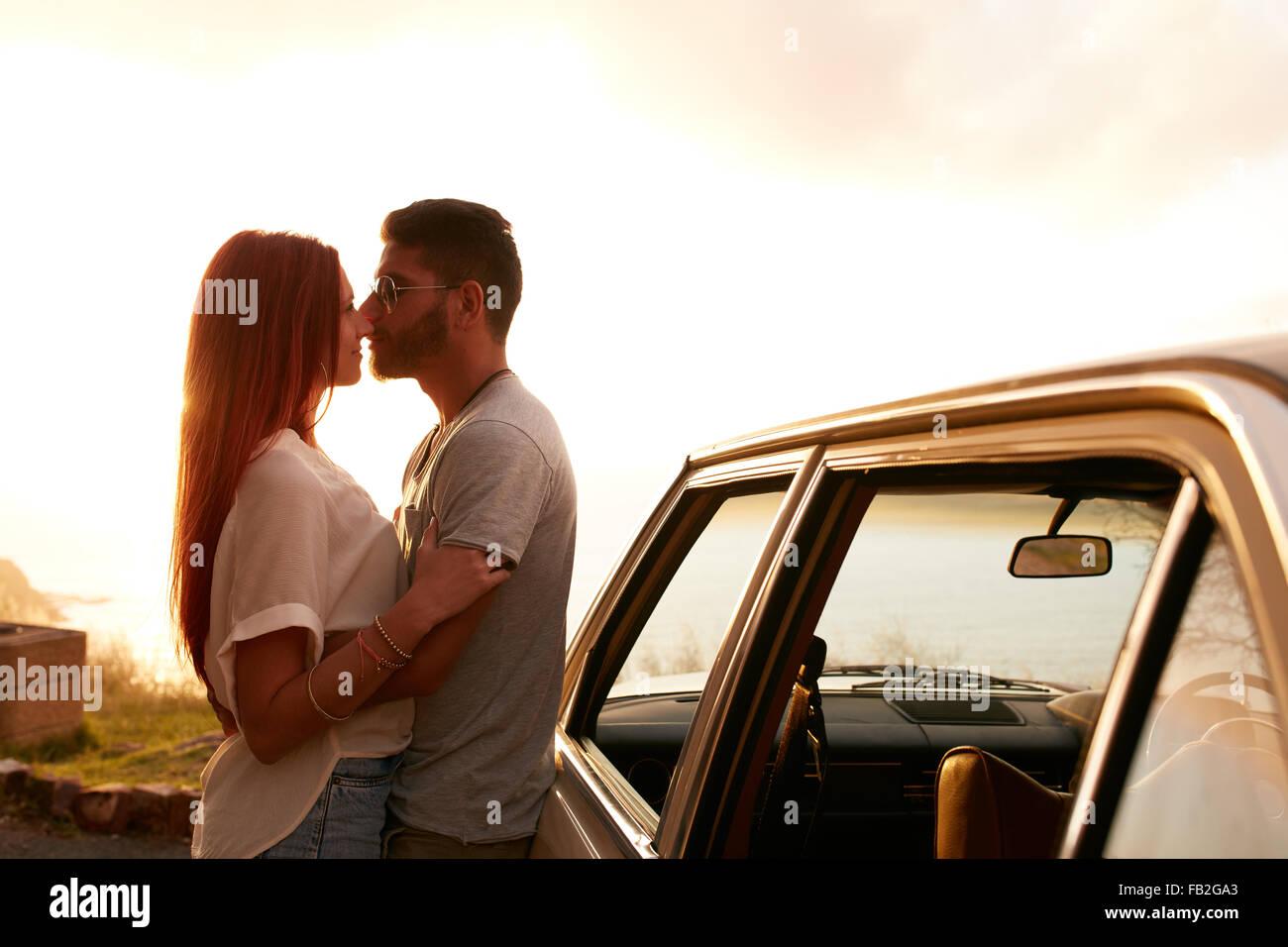 Couple debout près de leur voiture. Jeune homme et femme à propos d'embrasser, à l'extérieur. Photo Stock
