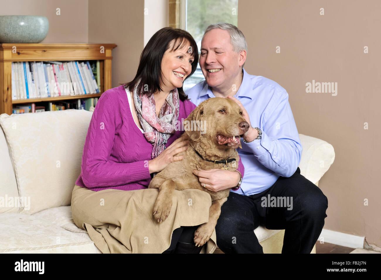 Un couple d'âge moyen s'est assis sur un canapé serrant son chien Photo Stock
