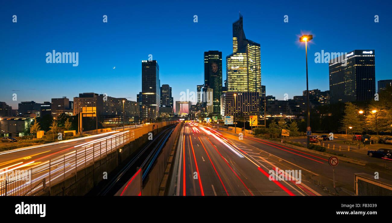 Route de Paris la nuit menant vers la Grande Arche et immeubles de bureaux modernes à la Defense, Paris, France Banque D'Images
