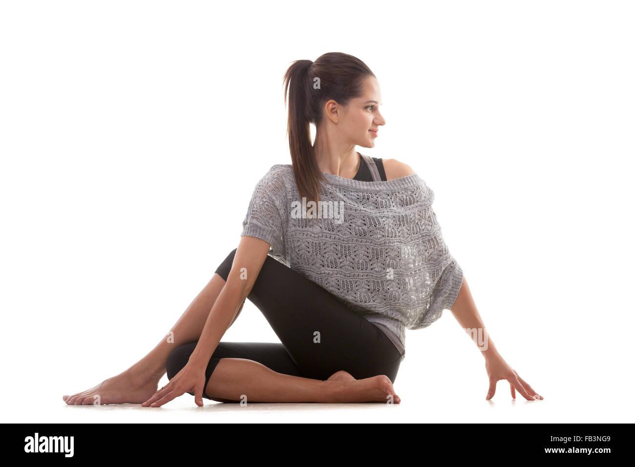Yoga sportif fille sur fond blanc l'exécution Ardha Matsyendrasana (moitié seigneur des poissons pose, Photo Stock
