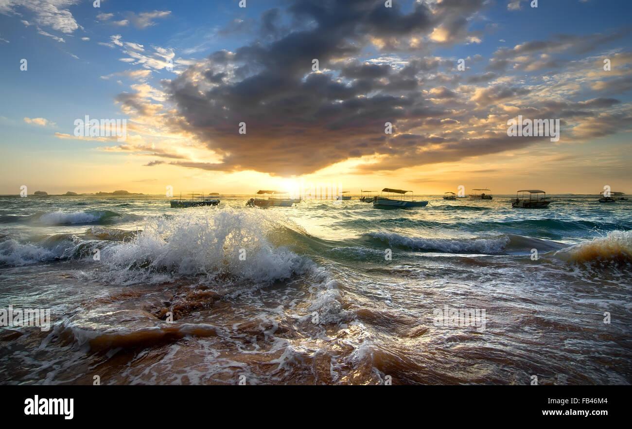 Bateaux de pêche dans l'océan au coucher du soleil Photo Stock