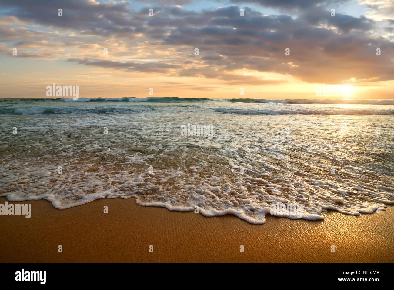 Coucher de soleil nuageux lumineux dans l'océan calme Photo Stock