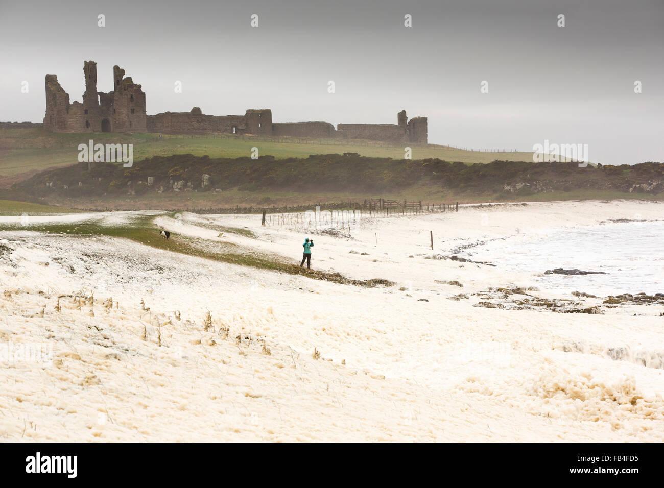 Une femme prépare la tempête entouré par wipped mousse par les vagues de tempête soufflant à Photo Stock