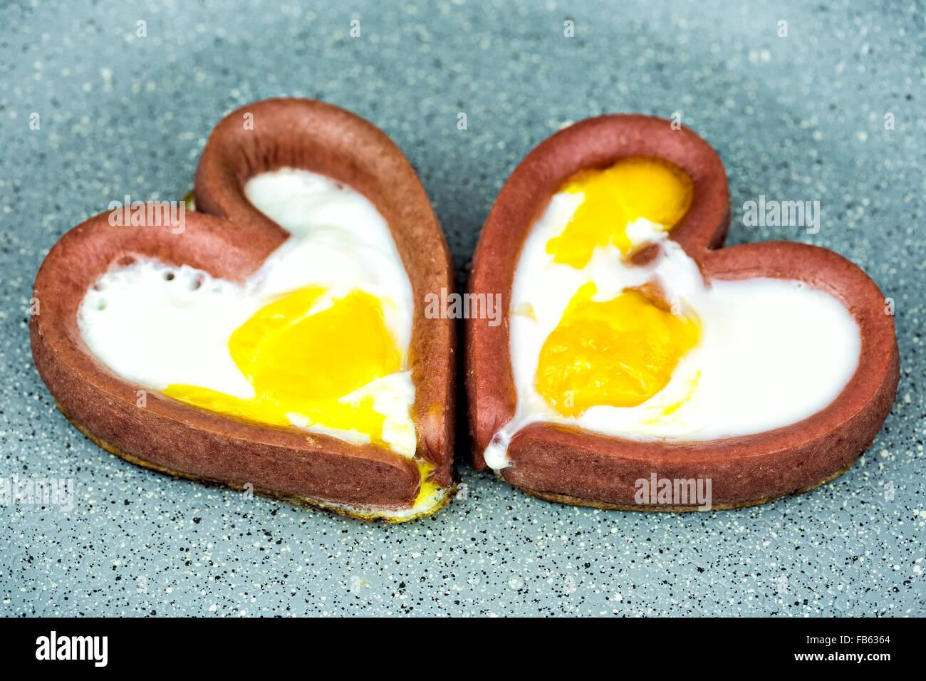 Couple d'oeufs la cuisson avec des saucisses en forme de cœur dans une poêle. La cuisson des oeufs au plat en forme Banque D'Images