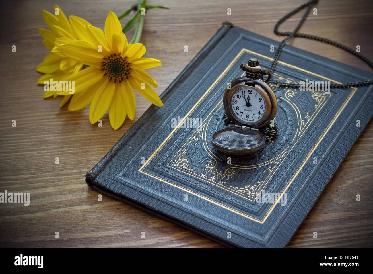 Vintage montre de poche et fleur jaune allongé sur le vieux livre Photo Stock