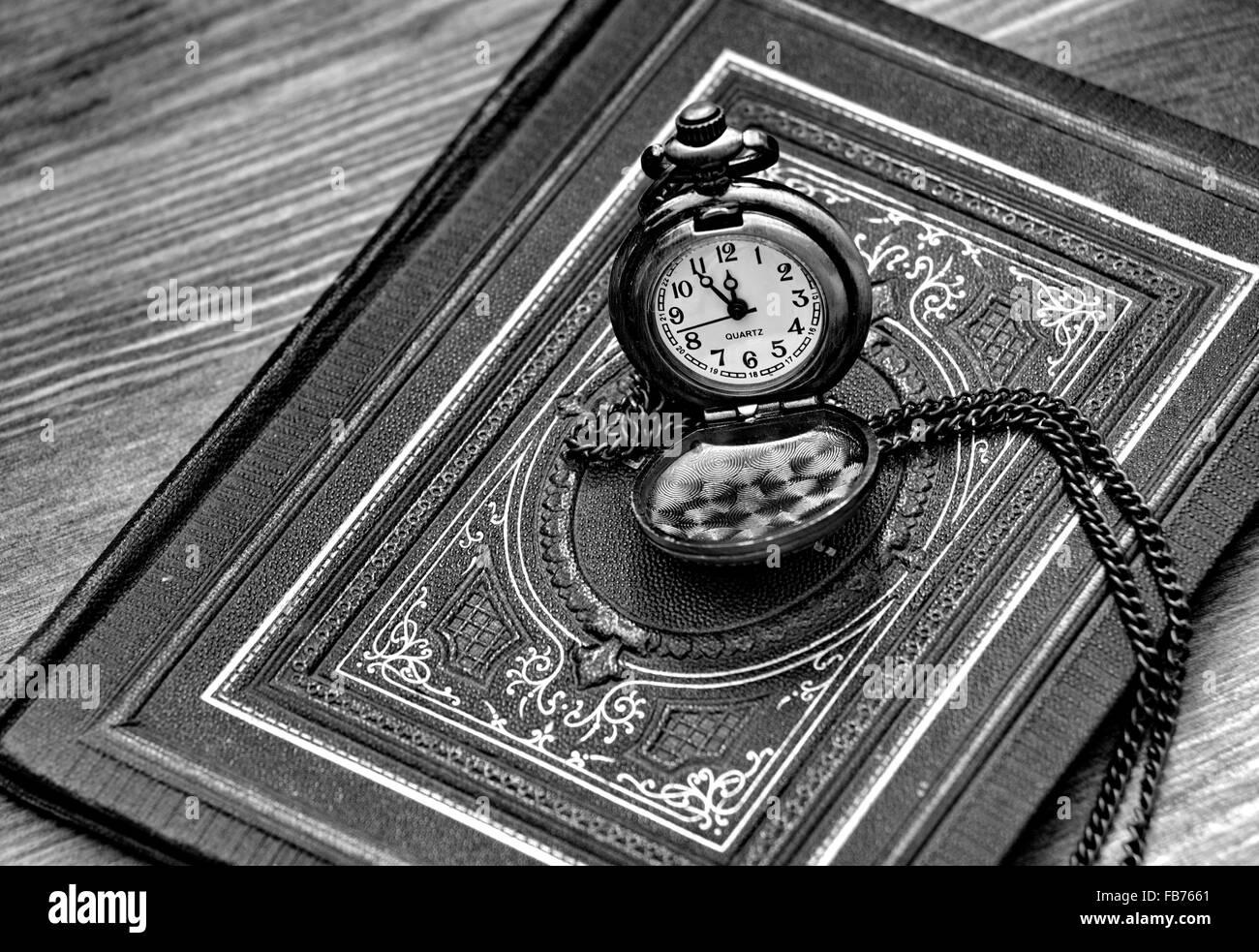 Montre de poche rétro allongé sur le vieux livre d'ornements, en noir et blanc Photo Stock