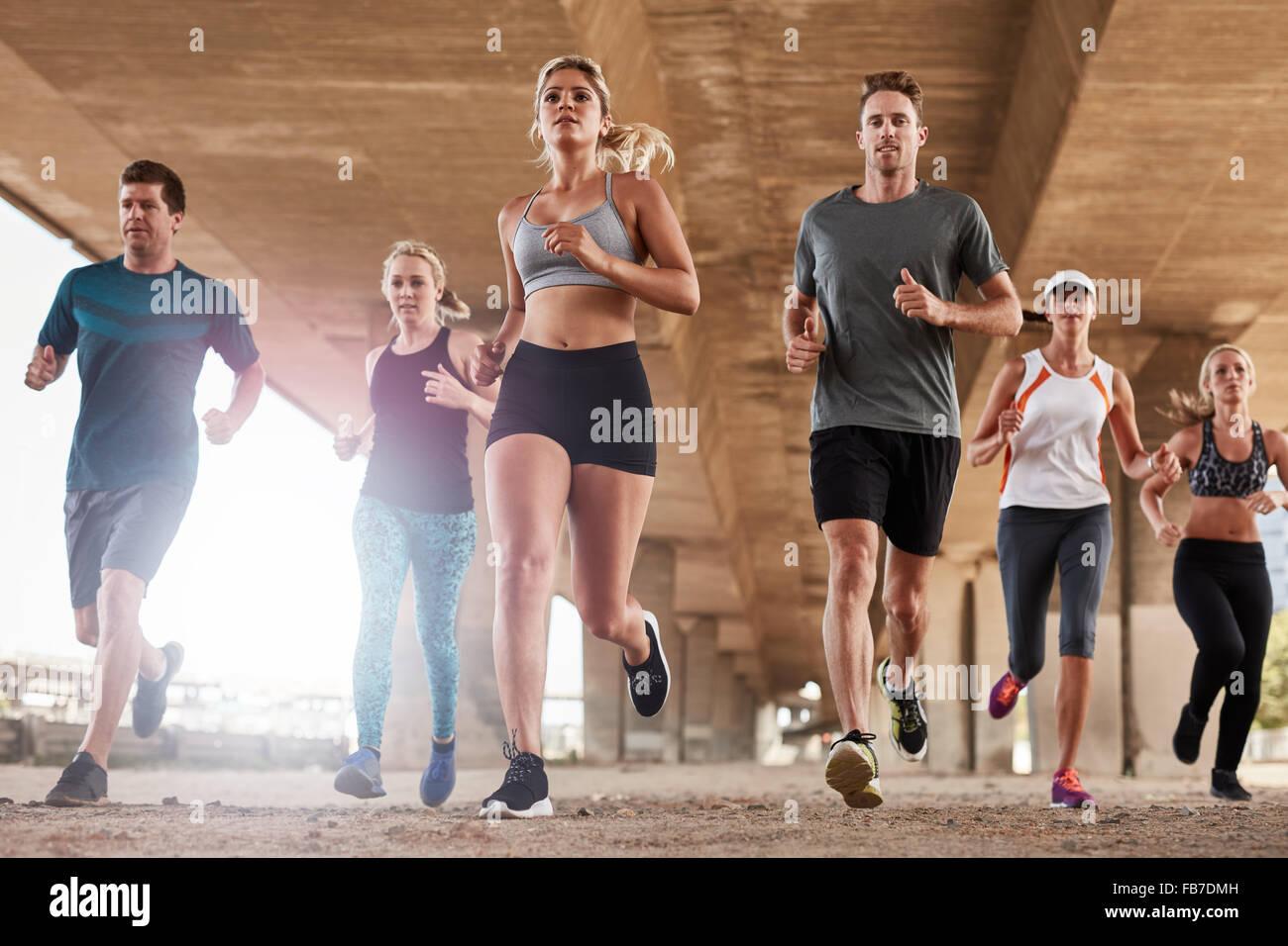 Groupe déterminé de jeunes fonctionnant ensemble en ville. Low angle view of running club membres formation Photo Stock