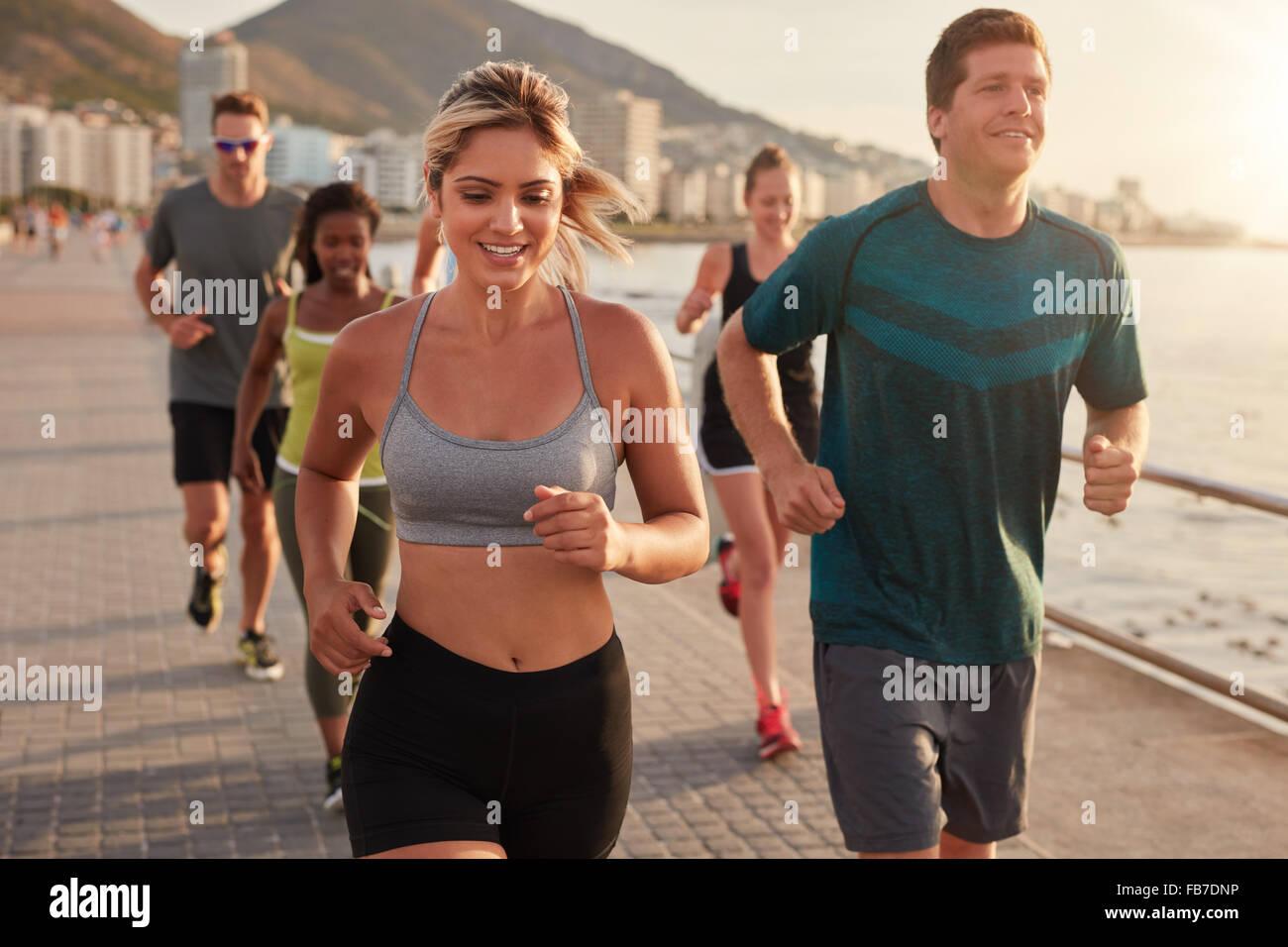 Portrait de jeune femme fit courir avec des amis sur la rue le long de la mer. Running club en formation de groupe Photo Stock