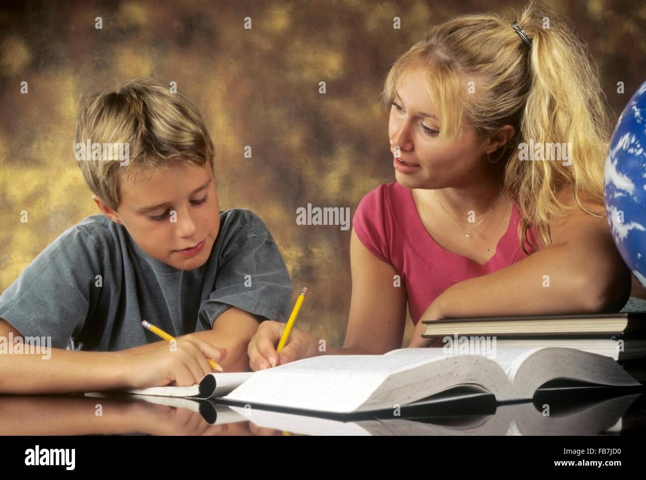 Grande sœur aider jeune frère étude Photo Stock