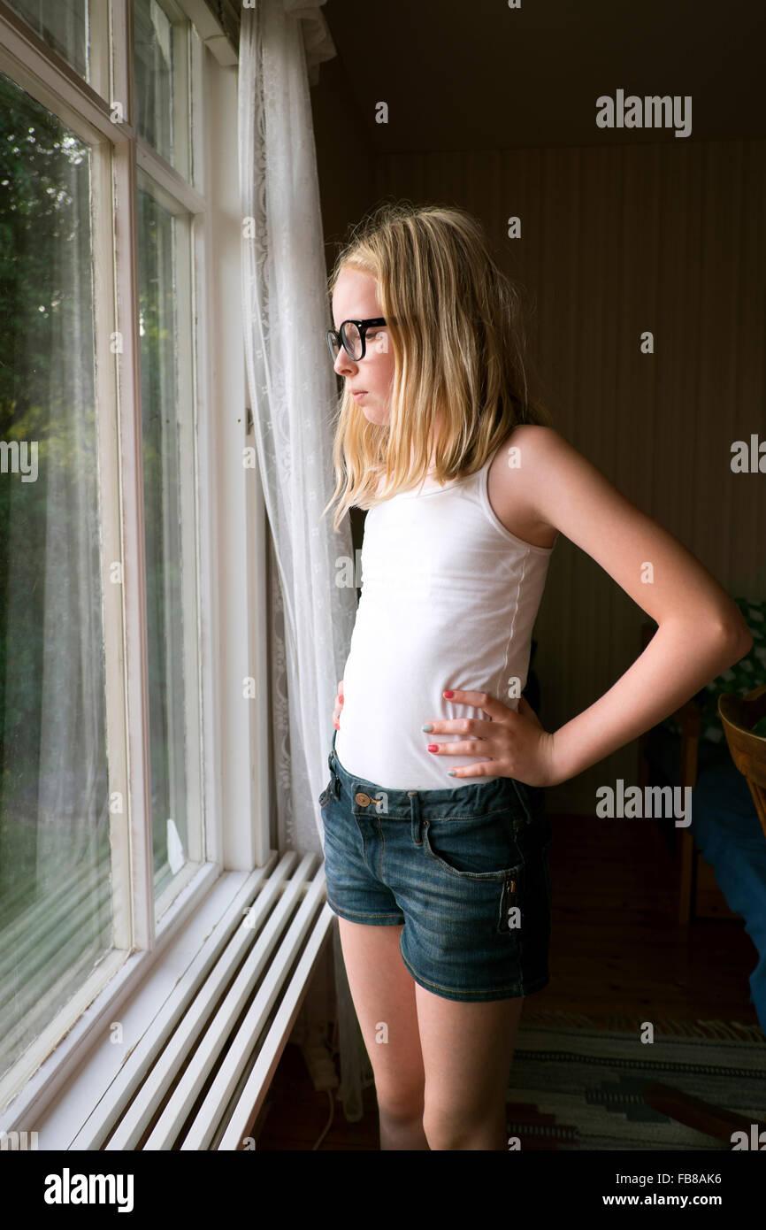 La Suède, Skane, Vejbystrand, Girl (10-11) à la fenêtre si Photo Stock