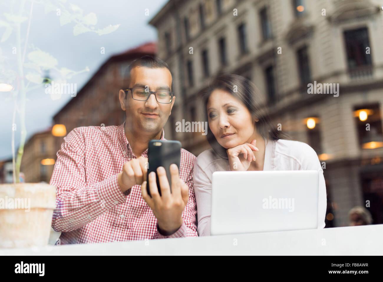 La Suède, l'Uppland, Stockholm, homme et femme, à l'aide de smart phone in cafe Photo Stock