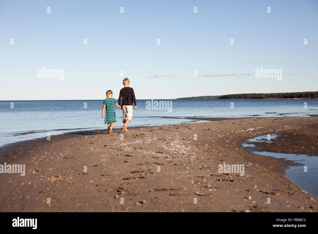 La Suède, Medelpad, Bergafjarden, Frère (10-11) avec sœur (6-7) marcher le long de la côte baltique Photo Stock
