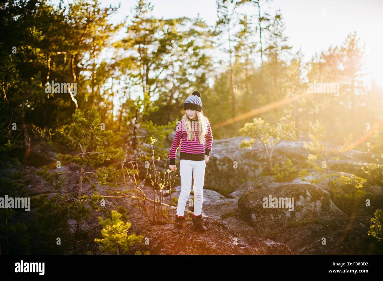 La Suède, Medelpad, Sundsvall, Juniskar, Portrait of Girl (10-11) standing in forest sur sunny day Banque D'Images