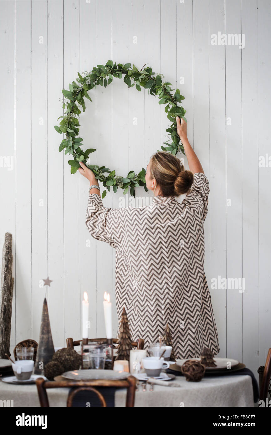 La Suède, Woman hanging Christmas wreath on wall Photo Stock