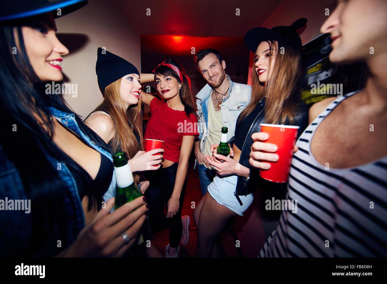 Les jeunes gens élégants avec boissons rassemblement dans bar Photo Stock