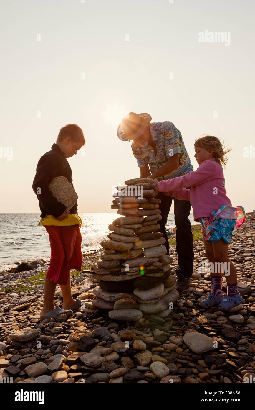 La Suède, Oland, Gronhogen, grand-père et ses petits-enfants (6-7), (10-11) faisant des tas de pierre Photo Stock