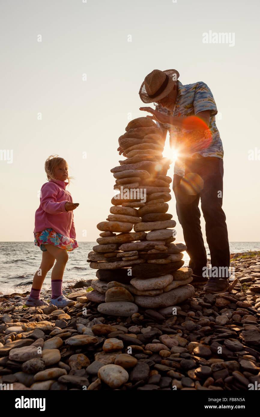 La Suède, Oland, Gronhogen, grand-père et sa petite-fille (6-7) faire des tas de pierre Photo Stock