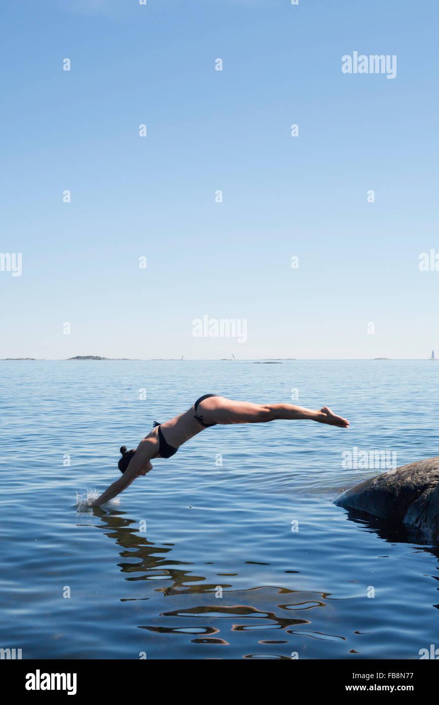 La Suède, l'Uppland, Runmaro Barrskar, femme, sauter dans sea Photo Stock