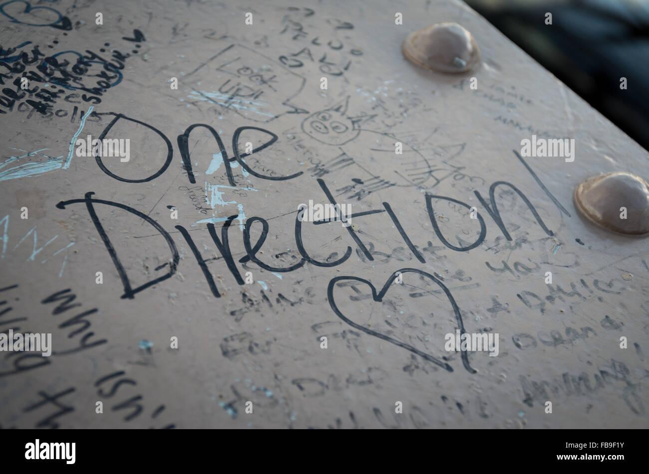 Une Direction fan des graffitis et coeur dessiné en feutre noir sur une poutre métallique Photo Stock