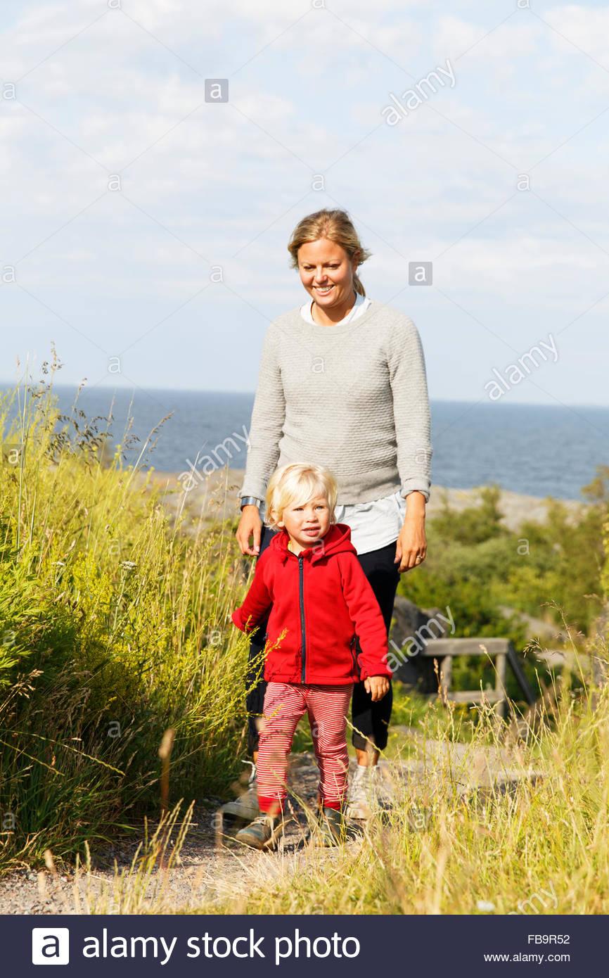 La Suède, l'archipel de Stockholm, Sodermanland, Oja, Woman walking with son (2-3) le long chemin à travers l'herbe Banque D'Images
