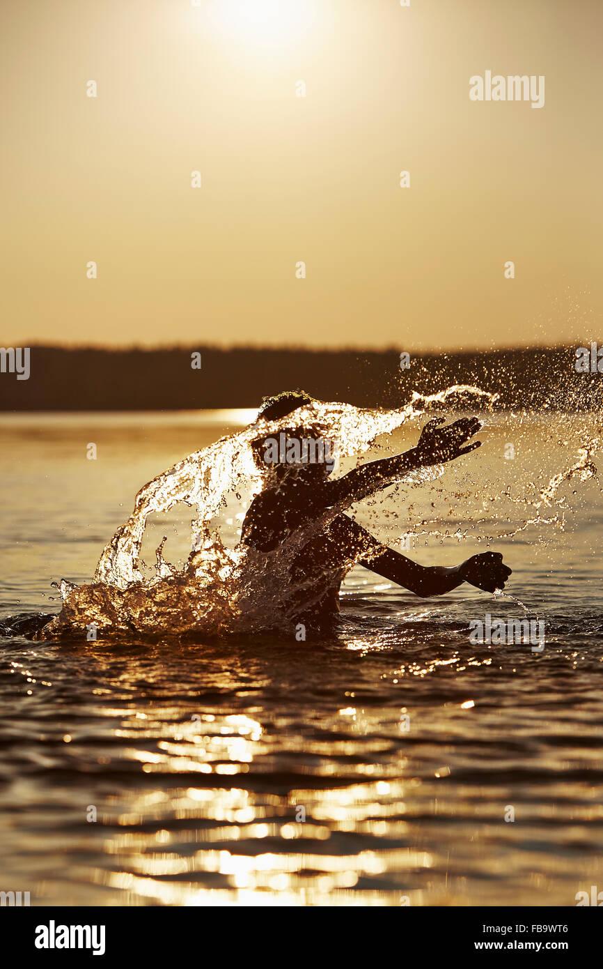La Suède, Vastra Sweden Skagern, Boy (10-11) La projection dans le lac au coucher du soleil Photo Stock