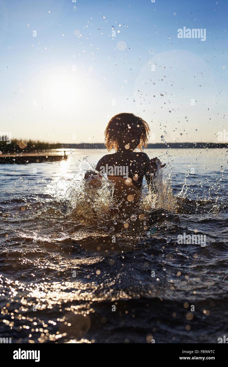 La Suède, Vastra Sweden Skagern, Girl (6-7) des éclaboussures dans le lac au coucher du soleil Photo Stock