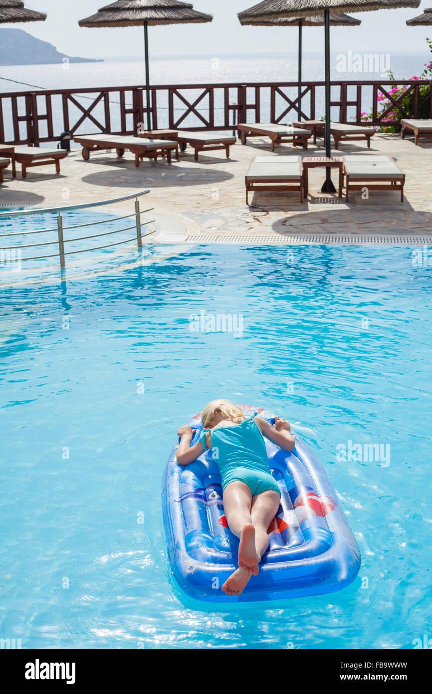 Grèce, Karpathos, Amopi, Girl (6-7) on pool raft Banque D'Images